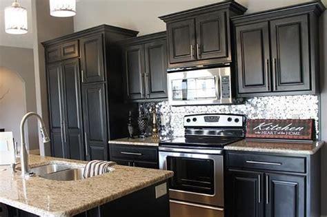 Black kitchen cabinets, granite top, and silver metallic