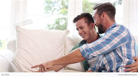 gay on the couch gay couple relaxing on the couch using laptop stock video