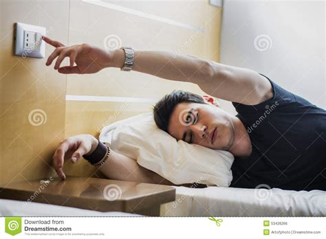 the bed guy tired guy switching off light while lying on bed stock