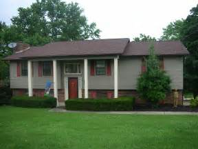 what color to paint brick house red brick with muted olive grey siding and red shutters