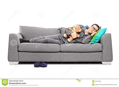 sleeping in sofa young man in pajamas sleeping on couch with teddy bear