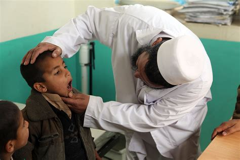 Physician Background Check File An Afghan Doctor Checks A Patient S Tonsils At A Clinic In Sarobi