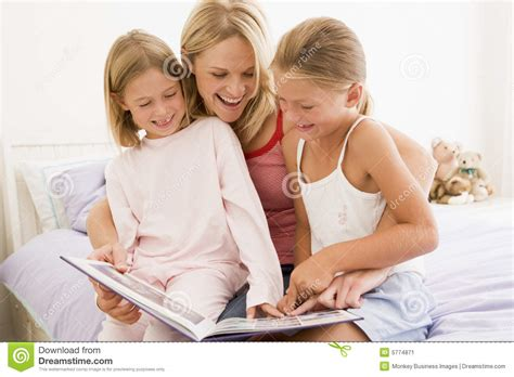 young woman bedroom woman and two young girls in bedroom reading book stock