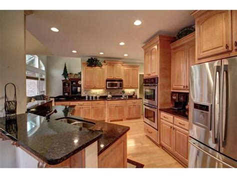 Downsized Appliances Light Wood Cabinetry And A Large Open   kitchen stainless steel dark granite counter tops light