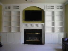 living room light brown wooden bookcase with shelves and grey fireplace plus grey rectangle tv