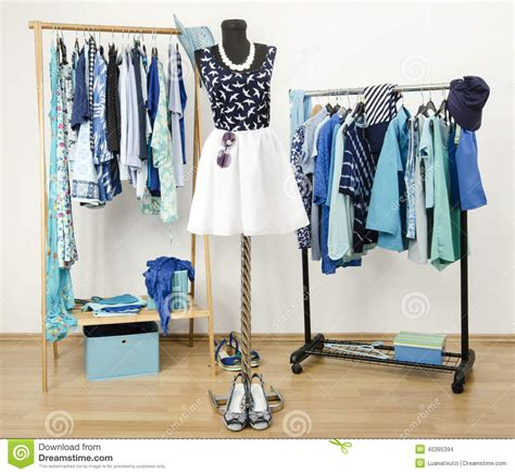 dressing closet with blue clothes arranged on hangers