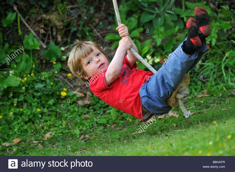 swinging on a rope boy on a rope swing child swinging on a rope stock photo