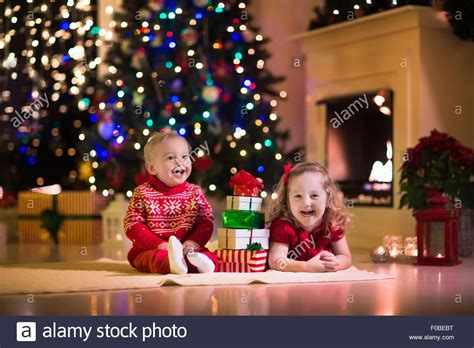 familyphotos of christmas tree cutting family on at fireplace opening presents stock photo royalty free image