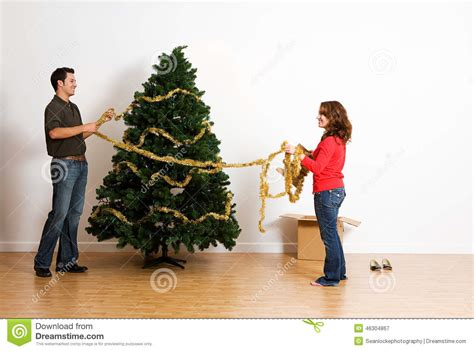 christmas putting tinsel or garland on tree stock photo