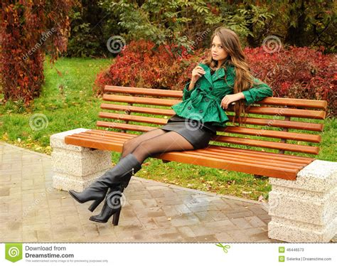 sitting on park bench girl sitting on a bench in the park stock photo image