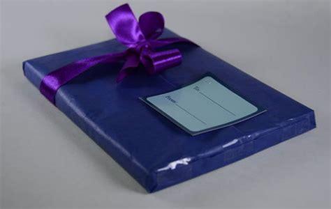 escolha um papel de presente com a esta que desejar e recorte a em como embrulhar livro ou cd dvd com papel de presente