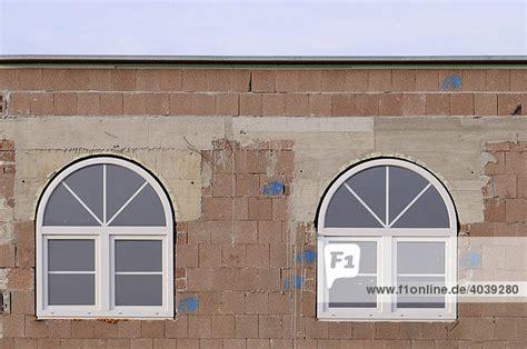 isolierfenster preise unverputzter rohbau mit neu eingebauten rundbogenfenstern