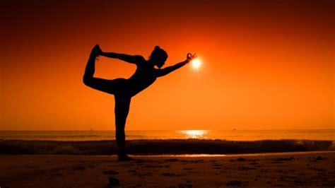 imagenes yoga en la playa mujer estirando su cuerpo en poses de yoga al atardecer en