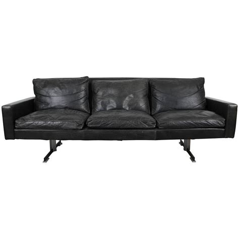 mid century modern black leather sofa with chrome legs at