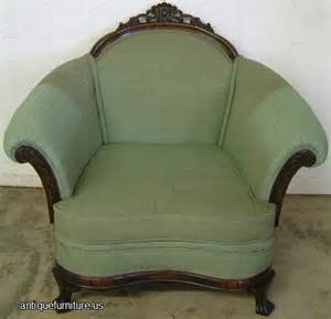 Antique upholstered 1920s easy chair with ornate carving at antique