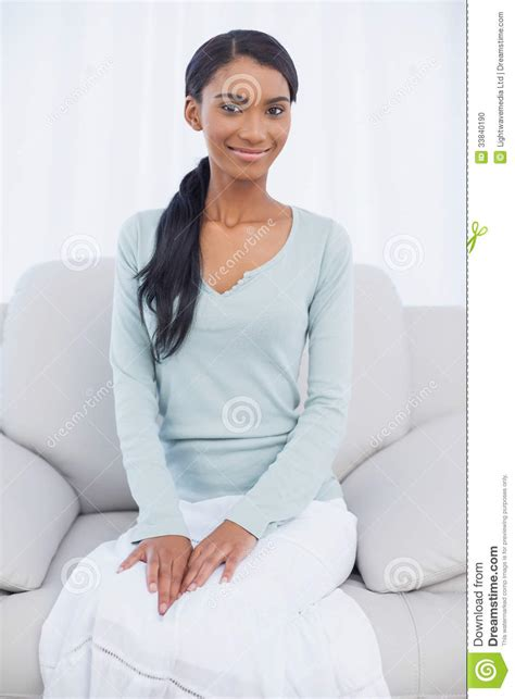woman grows into couch attractive woman sitting on cosy sofa stock photo image