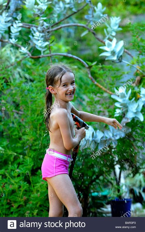7 year old girl stock photo seven year old girl playing with hose in backyard garden