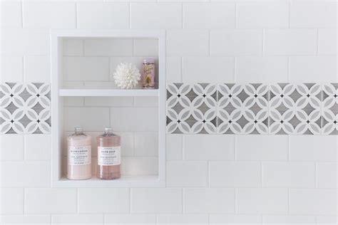White shower tiles with gray border tiles framing tiled shower niche transitional bathroom