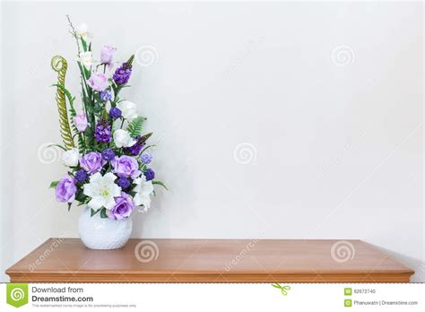 flower on table artificial flower vase on wooden table and white wall