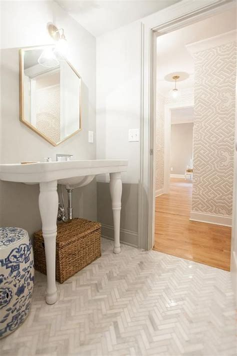 beautiful powder room features a gold hexagon mirror