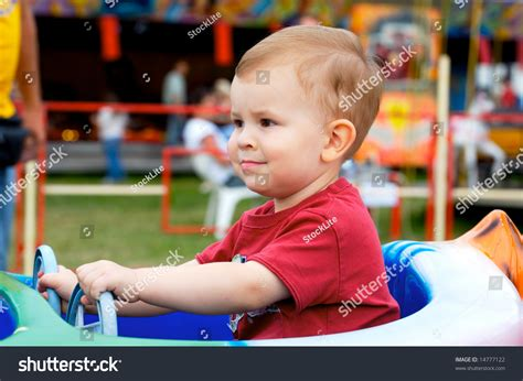 theme park for 2 year old two years old child driving toy vehicle in the amusement