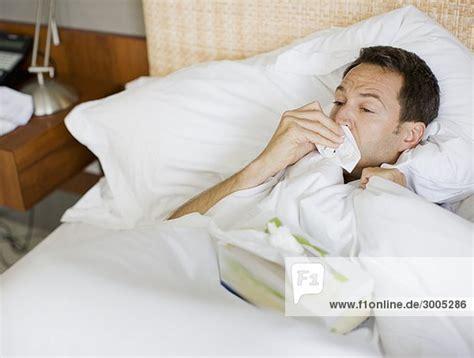 mann im bett kranker mann im bett putzt die nase lizenzfreies bild