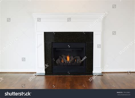 horizontal photo of a gas fireplace with a white