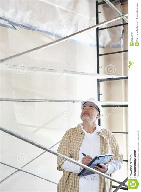 male architect with digital tablet studying plans in male architect making a note in digital tablet pc while
