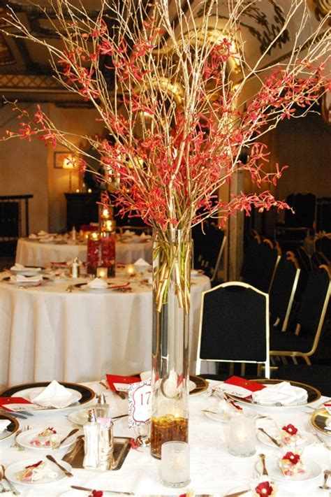 tall centerpieces of chic gold branches and red mokara