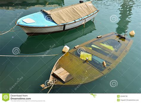 boat sinking in your dream two boats on berth one is sinking stock photo image