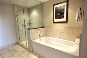 Is a extra large bathroom with separate bathtub and glassed in shower