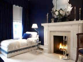 Navy blue bedroom with white fireplace and chaise lounge hgtv