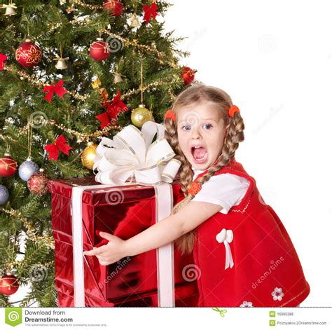 child holding gift box by christmas tree stock photo