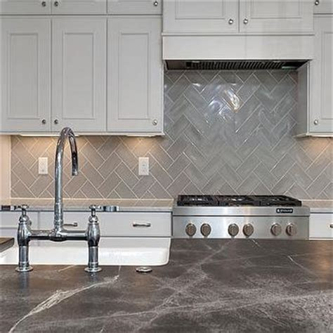 white kitchen cabinets with gray chevron tile backsplash