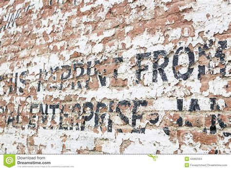 wall writing old weathered brick wall with advertisement stock photo