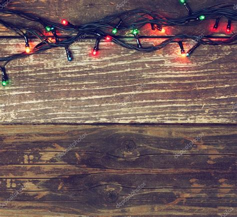 colorful christmas lights on wooden rustic background