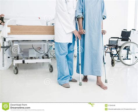sectioning a patient doctor helping patient in crutches at the hospital royalty