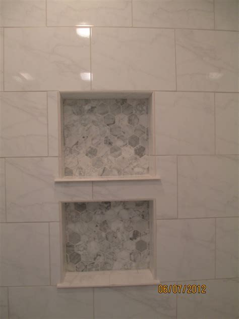 hexagon carrara marble tile in back of shower niche