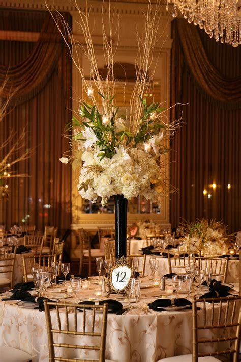 white and gold table l black centerpiece arrangement with white flowers and