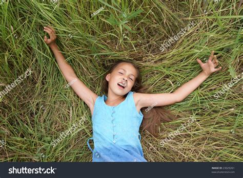 pre non girls smiling preteen girl lying on green stock photo 23029261