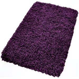 Bath rug in a shag style with deep dark and medium tone purple colors