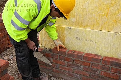 a026 00968 bricklayer with trowel building a cavity wal