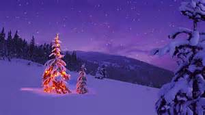christmas tree glowing on a snowy mountain side stock