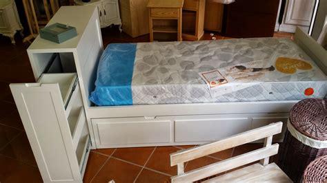 cama nido tiene de original el baul cabecero  dos cajones  abren lateralmente sobre unas