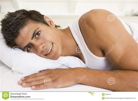 lying or laying in bed man lying in bed smiling royalty free stock photography