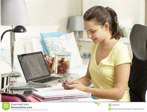 girl with mobile phone in bedroom stock photo image teenage girl studying at desk in bedroom using mobile