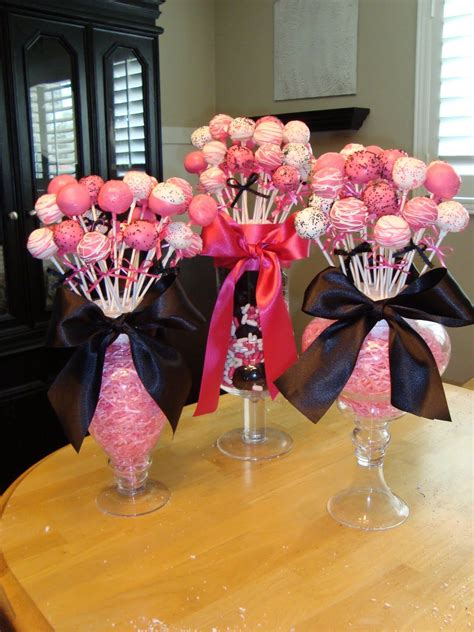 bridal shower cupcake toppers by a lollipop tree cake pops or lollipops in jars are stuck in styrofoam balls the balls are surrounded by