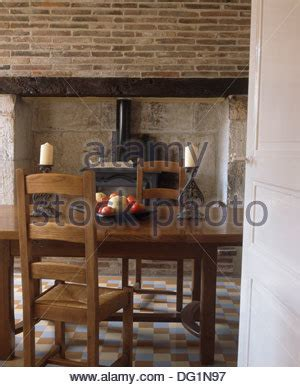 dining table in front of fireplace wood burning stove in exposed brick fireplace in a cottage