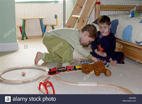 in their bedroom two young boys playing with train set and toys in their bedroom one stock photo