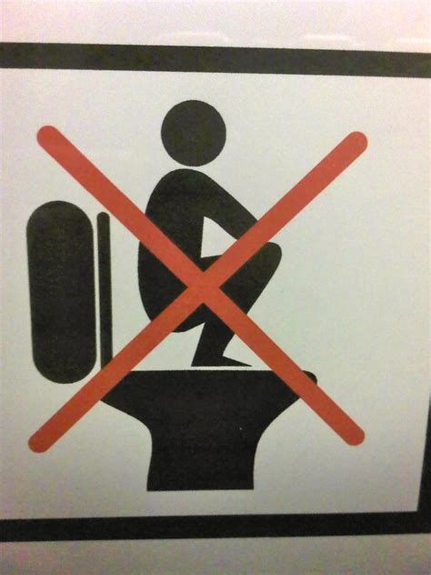 asians stand on toilet bowls sign in bold font do not